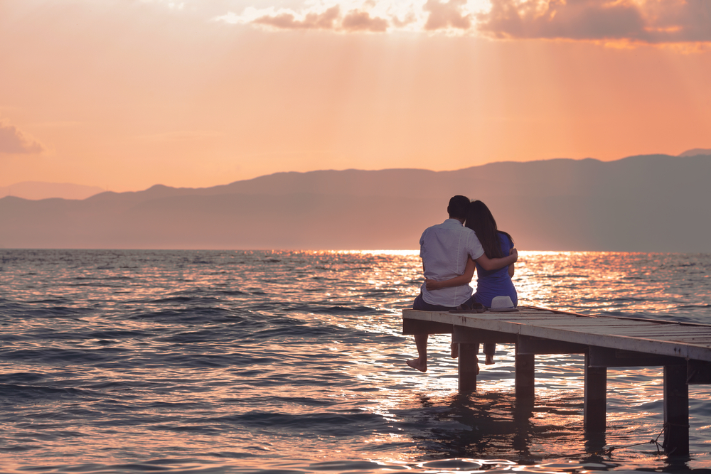 Man and woman sitting on pier